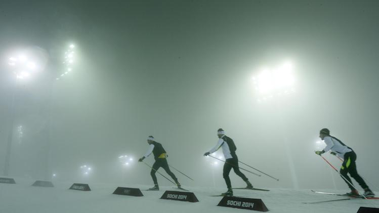 Athletes ski through the stadium after the men's biathlon 15K mass start race was postponed due to fog at the 2014 Winter Olympics, Sunday, Feb. 16, 2014, in Krasnaya Polyana, Russia