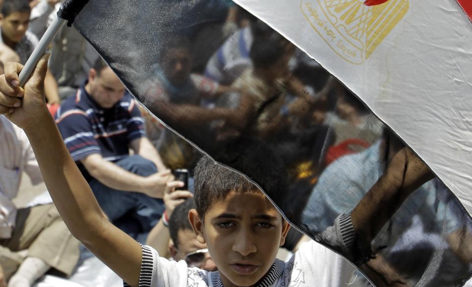 A boy holds an Egyptian flag as he attends Friday prayers in Tahrir Square in Cairo,  Friday, July 1, 2011.  (AP Photo/Sergey Ponomarev)
