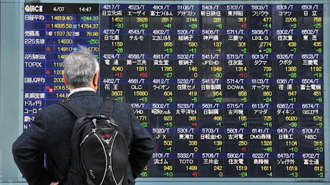 A pedestrian stands in front of a share price board in Tokyo on April 7, 2014