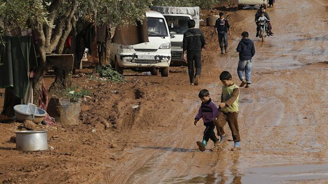 In this Tuesday, Feb. 19, 2013 photo, Syrian refugees walk on a mud road at Atmeh refugee camp, in the northern Syrian province of Idlib, Syria. This rebel-controlled camp only yards from the border with Turkey houses some 16,000 people displaced by the civil war. But the U.N. and other major aid agencies best equipped to handle such a large-scale relief agency cannot reach them because they are inside Syria. That leaves the job to smaller organizations who can only provide a fraction of the needs. (AP Photo/Hussein Malla)