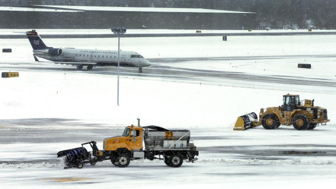 FILE - In this Thursday, Dec. 27, 2012 file photo, snow is cleared on a runway as a plane taxis into Manchester-Boston Regional Airport in Manchester, N.H. As the Northeast braces for its largest winter storm in more than a year, airlines are already employing a strategy that has served them well in recent years: Cancel flights early and keep planes, crews and passengers away from snowed-in airports. (AP Photo/Elise Amendola, File)