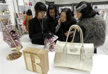 A saleswoman for British fashion brand Mulberry talks about one of the brand's bags to customers at a shop at Lotte Premium Outlets in Paju, north of Seoul, December 7, 2011. REUTERS/Jo Yong-Hak