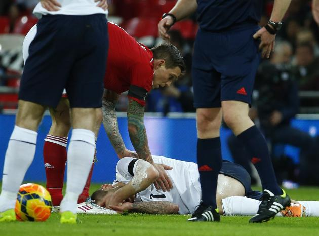 England's Jack Wilshere reacts after being fouled by Denmark's Daniel Agger during their international friendly soccer match at Wembley Stadium in London