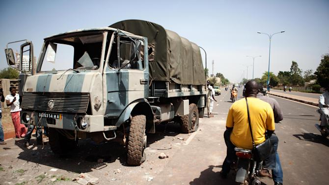Passerby stop to look at a military truck, damaged in inter-army fighting earlier that morning, outside the paratrooper camp which is home to former president's Red Beret presidential guard, in Bamako, Mali, Friday, Feb. 8, 2013. Soldiers from a unit allied with the leader of last year's military coup in Mali stormed the camp of the former president's guard Friday morning, and at least one person was killed and five were wounded, witnesses said. The bloodshed underscores that Mali's military is in disarray and in poor shape to confront without outside help the well-armed Islamists, many of whom have combat experience.(AP Photo/Thomas Martinez)