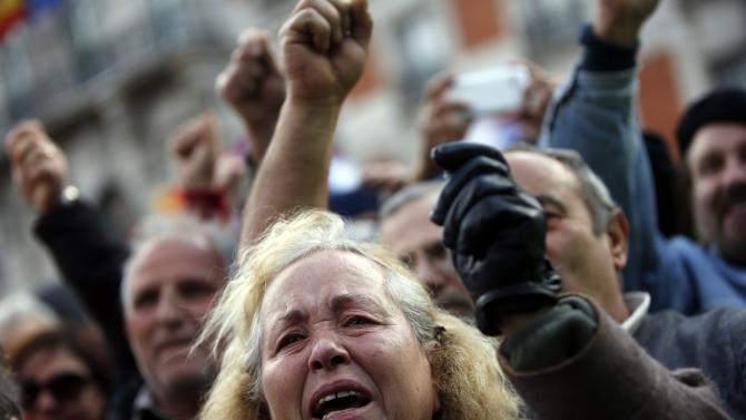 A woman gets emotional as she takes part in a rally  called by Podemos at Madrid's Puerta del Sol landmark