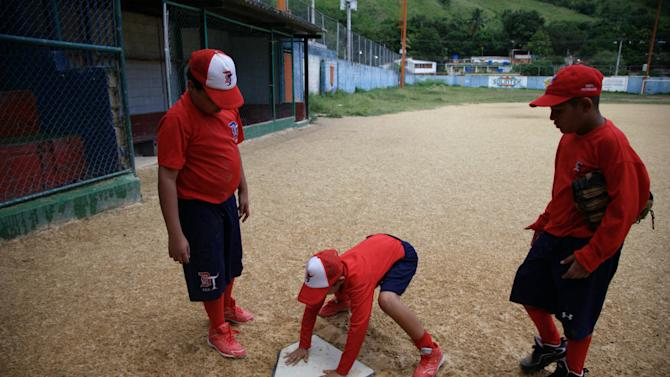 In this Oct. 25, 2012 photo, boys prepare for training at a baseball school in Maracay, Venezuela.  Many of the boys are inspired by the example of Detroit Tigers slugger Miguel Cabrera, who learned the game on this very field. Their baseball school in the poor neighborhood where Cabrera grew up is one of many across Venezuela, a web for training young ballplayers that has made the country a powerhouse in the U.S. major leagues. (AP Photo/Ariana Cubillos)