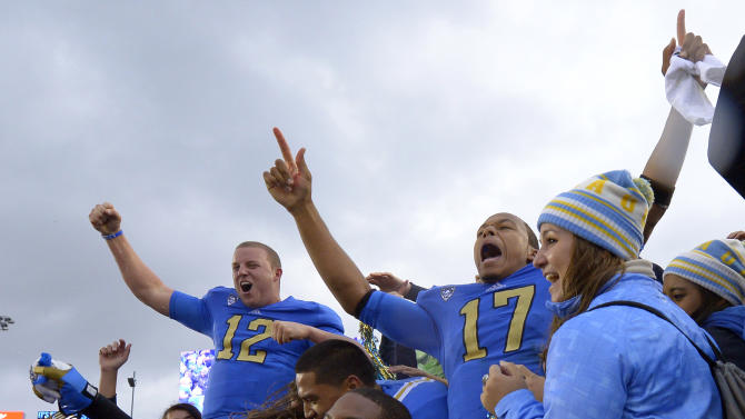 UCLA quarterback Brett Hundley, right, celebrates with teammates Richard Brehaut (12) and Shaquelle Evans (1) and fans after they defeated Southern California 38-28 in an NCAA college football game, Saturday, Nov. 17, 2012, in Pasadena, Calif.  (AP Photo/Mark J. Terrill)
