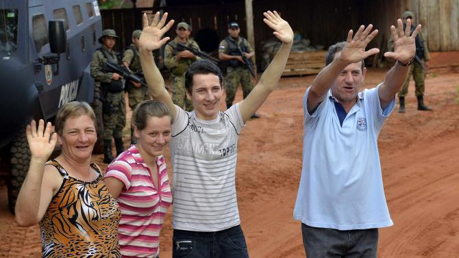 Arlan Fick, son of Brazilian immigrants to Paraguay, waves to the press as he stands with his family to give a press conference a day after he was released by his kidnappers, on their ranch in Paso Tuya