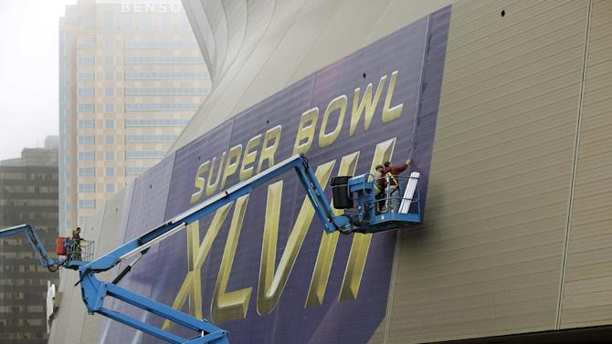 """In this Jan. 15, 2013, photo, workers put up signage for the upcoming Super Bowl on the Superdome in New Orleans. With the Super Bowl in New Orleans Feb. 3 and Mardi Gras falling just nine days later, the city is gearing up for a massive celebration and influx of tourists that locals are calling """"Super Gras."""" (AP Photo/Gerald Herbert)"""