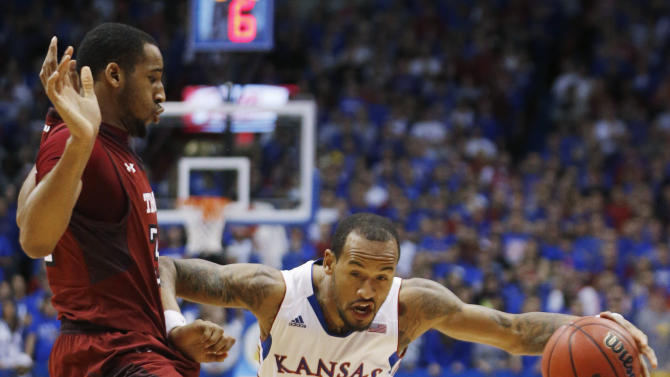 Kansas guard Travis Releford (24) works against Tempe forward Rahlir Hollis-Jefferson during the first half of an NCAA college basketball game in Lawrence, Kan., Sunday, Jan. 6, 2013. (AP Photo/Orlin Wagner)