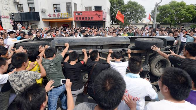 In this Sept. 15, 2012 photo, anti-Japan demonstrators overturn a Japanese-made car in Suzhou in Jiangsu Province, China. Sales of Toyota and Honda vehicles nosedived in China during September as anti-Japanese sentiment flared over a territorial dispute that threatens to hobble what was a booming business relationship between Japan and its biggest export market. Toyota Motor Corp. said Tuesday, Oct. 9, that sales of new vehicles in China dropped 48.9 percent in September from a year earlier to 44,100 vehicles. Honda Motor Co. said September sales plunged 40.5 percent to 33,931 vehicles. China sales for Nissan Motor Co. slid 35.3 percent last month to 76,100 vehicles. (AP Photo/Kyodo News) JAPAN OUT, MANDATORY CREDIT, NO LICENSING IN CHINA, FRANCE, HONG KONG, JAPAN AND SOUTH KOREA