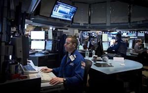Traders work on the floor of the New York Stock Exchange at the opening bell in New York