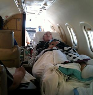 This Aug. 23, 2011 photo provided by Jennifer Mactagone shows her son, Jesse Mactagone, 14, in a medical plane en route from Kansas back home to Auburn, Calif. Both of the boy's legs were broken during the four days in August 2011 that he attended St. John's Military School in Salina, Kan. Jennifer Mactagone says a cellphone video, obtained exclusively by The Associated Press, depicting her son struggling to stand on two broken legs is proof that her son was harmed while attending a the military school and supports claims in a federal lawsuit that the school encouraged a culture of abuse. (AP Photo/Jennifer Mactagone)