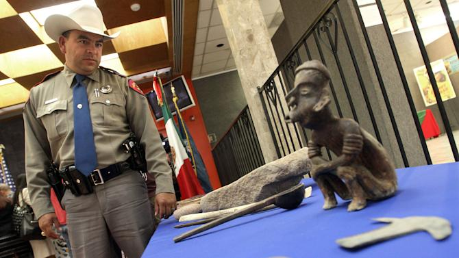 Trooper John Albert Barragan, left, who worked with Homeland Security Investigators, looks at a table with Mexican artifacts during a news conference at the Mexican Consulate in El Paso, Texas, Thursday, Oct. 25, 2012. More than 4,000 archaeological artifacts looted from Mexico and seized in the U.S. were returned to Mexican authorities on Thursday in what experts say is one of the largest repatriation ever made between the neighboring countries. (AP Photo/The El Paso Times, Mark Lambie)