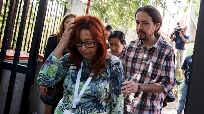 Podemos (We Can) leader Iglesias leaves with his mother after casting his vote at a polling station during regional and municipal elections in Madrid