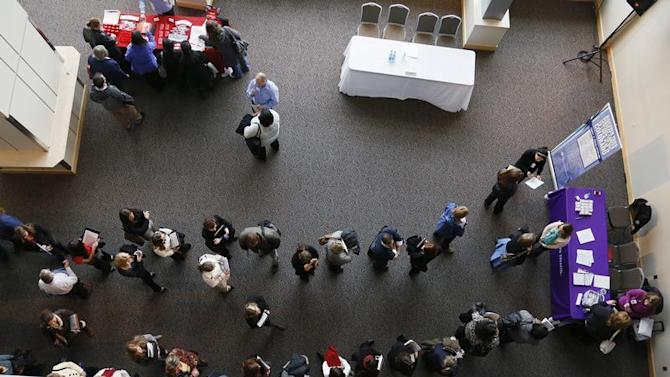Hundreds of job seekers wait in line with their resumes to talk to recruiters at the Colorado Hospital Association health care career fair in Denver