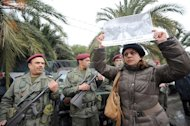 Tunisian soldier stand guard as a woman holds up a poster featuring late opposition leader Chokri Belaid during his funeral procession in Tunis, on February 8, 2013. Tunisian police have fired tear gas and clashed with protesters as tens of thousands joined the funeral of Belaid whose murder plunged the country into new post-revolt turmoil