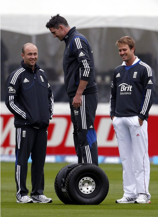 England cricket team player Pietersen rides a Segway next to teammates Trott and Compton during a rain delay on the first day of the first test against New Zealand at the University Oval in Dunedin