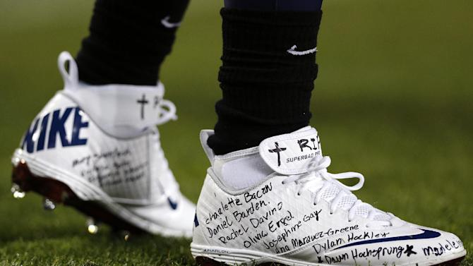 Tennessee Titans running back Chris Johnson wears a pair of shoes with the names of the victims of the Sandy Hook Elementary School shootings in Newtown, Conn., during warmups before an NFL football game against the New York Jets, Monday, Dec. 17, 2012, in Nashville, Tenn. (AP Photo/Joe Howell)