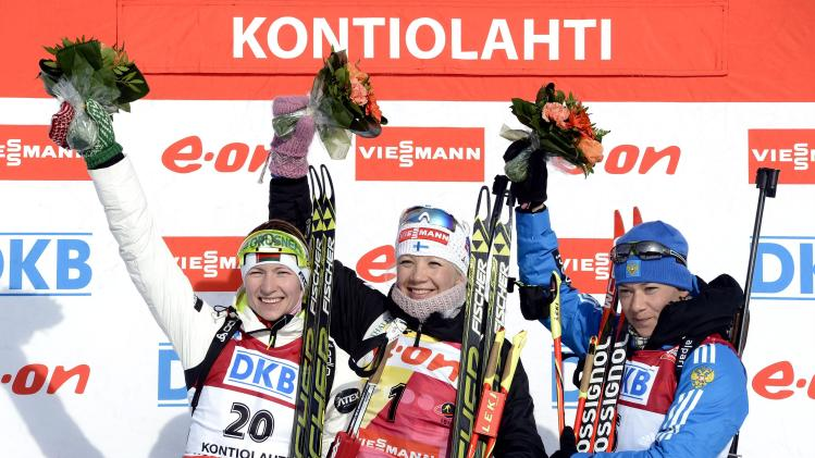 Finland's Makarainen celebrates winning next to Domracheva of Belarus and Zaitseva of Russia on the podium of the women's 10 km pursuit competition of the IBU World Cup Biathlon event in Kontiolahti