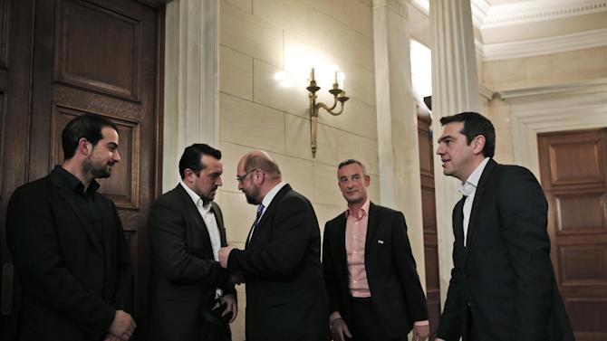 Greek Prime Minister Alexis Tsipras, right, looks on as European Parliament President Martin Schulz, center, shakes hands and talks with Greek Minister of State Nikos Pappas, second left, following a news conference after their meeting at Maximos Mansion in Athens, Thursday, Jan. 29, 2015. Schulz is the first European Union official to meet Tsipras, whose new Cabinet alarmed the Greek stock market Wednesday with promises to renege on a series of key budget commitments made by previous administrations in exchange for 240 billion euros in rescue loans. (AP Photo/Lefteris Pitarakis)