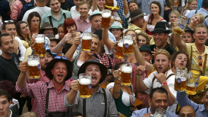 Visitors toast with their one-liter beer mugs during opening day of 181st Oktoberfest in Munich