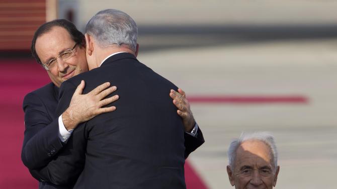 French President Francois Hollande, left, hugs Israel's Prime Minister Benjamin Netanyahu as Israel's President Shimon Peres sits upon his arrival in Ben Gurion airport near Tel Aviv, Israel, Sunday, Nov. 17, 2013. (AP Photo/Ariel Schalit)