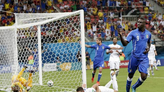 Italy's Mario Balotelli (9) celebrates after getting the ball past England's goalkeeper Joe Hart, left, and Gary Cahill, center, to score his side's second goal during the group D World Cup soccer match between England and Italy at the Arena da Amazonia in Manaus, Brazil, Saturday, June 14, 2014