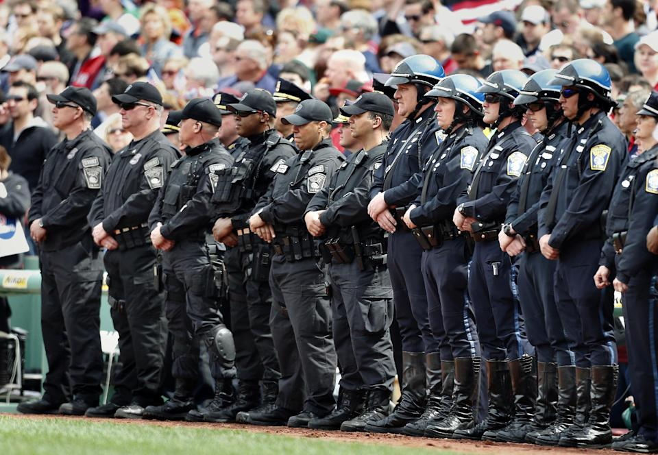 Boston police personnel stand on the field during ceremonies in honor of victims of and first responders to the Boston Marathon bombings, before a baseball game between the Boston Red Sox and the Kansas City Royals in Boston, Saturday, April 20, 2013. (AP Photo/Michael Dwyer)