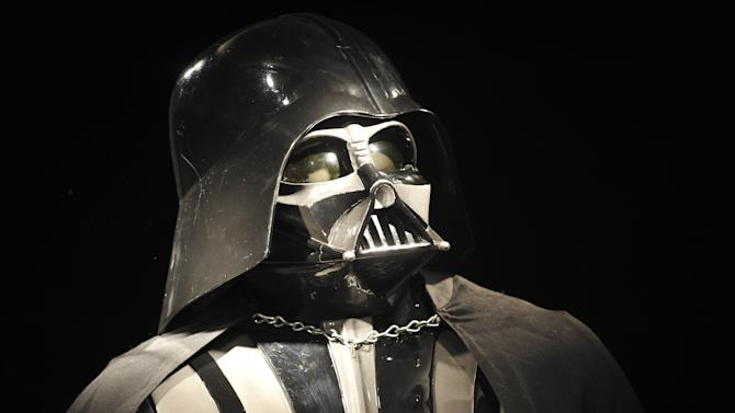 """FILE - In this Oct. 27, 2010 file photo, a Darth Vader costume produced for the second Star Wars movie """"The Empire Strikes Back,"""" released in 1980, is on display at Christie's auction house in London. For Star Wars fans, there has been a lot of speculation about what direction the series will take ever since Disney announced in October 2012 that it would buy Lucasfilm for $4.05 billion and resume making """"Star Wars"""" movies, starting with Episode 7 in 2015. (AP Photo/Lennart Preiss, File)"""