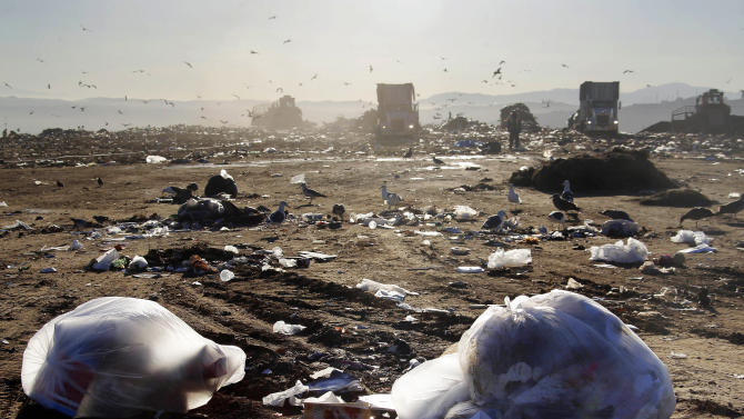 Trucks dump trash at the Puente Hill Landfill in Puente Hills, Calif. on Thursday, October 31, 2013. The nation's largest landfill 20 miles east of Los Angeles where 130 million tons of garbage have been dumped is closing Thursday after more than a half-century of service. (AP Photo/Nick Ut)