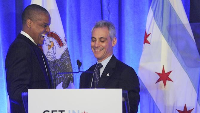 Chicago Mayor Rahm Emanuel, right, is introduced by Loop Capital Chairman and CEO James Reynolds Jr. left, during a luncheon at the Chicago Hilton in Chicago, Wednesday, April 10, 2013, before first lady Michelle Obama spoke. The first lady is visiting Chicago for a discussion with Emanuel and civic leaders on ways to combat youth violence. (AP Photo/Paul Beaty)