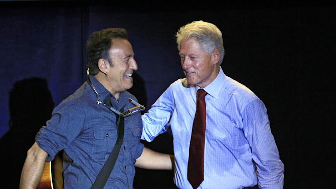 FILE - In this Oct. 18, 2012 file photo, former President Bill Clinton greets singer/songwriter Bruce Springsteen at a campaign event for President Barack Obama, in Parma, Ohio. Dozens of celebrities, elected officials, and others are blitzing through battleground states in the White House race's final days. Their goal: give the presidential campaigns a daily presence in key states even when the men at the top of the ticket (and their running mates) pitch for votes elsewhere. (AP Photo/Tony Dejak, File)