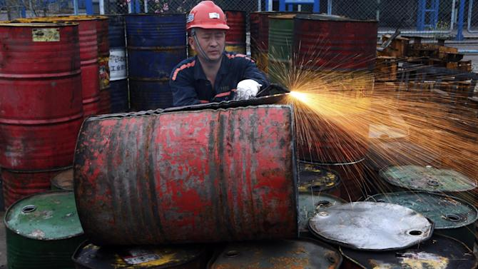 In this Tuesday, March 31, 2015 photo, a worker cuts open an oil barrel in a factory to recycle the metal in manufacturing water tanks in Huaibei in central China's Anhui province. China and Japan reported gloomy industrial data Wednesday, April 1, 2015, adding to pressure on leaders of the world's second- and third-largest economies to launch new stimulus. (AP Photo) CHINA OUT