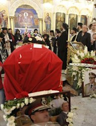 Soldiers and relatives of the late Syrian Defense Minister, General Daoud Rajha (portrait), attend his funeral at the Church of the Holy Cross in Damascus