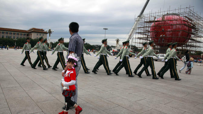 FILE - In this file photo taken Friday, Sept. 16, 2011, a Chinese girl in ethnic minority costume walks past Chinese paramilitary police marching across Tiananmen Square near the Great Hall of the People where the annual National People's Congress is held in March in Beijing, China. A glance at history suggests it's easier for a Chinese woman to orbit Earth than to land a spot on the highest rung of Chinese politics. In June, the 33-year-old Air Force major marked a major feminist milestone by becoming the first Chinese woman to travel in space. With a once-a-decade leadership transition set to kick off Nov. 8, many now are waiting to see if another ambitious Chinese female, State Councilor Liu Yandong, can win one of the nine spots at the apex of Chinese power.  (AP Photo/Ng Han Guan, File)