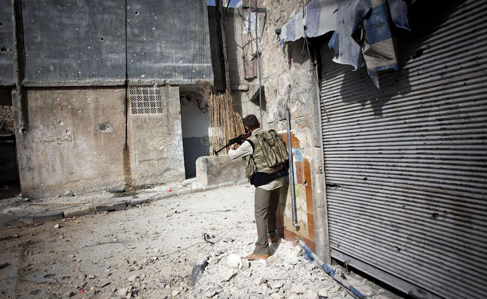 A Free Syrian Army fighter fires his weapon toward Syrian Army positions in Karmal Jabl district in Aleppo, Syria, Sunday, Oct. 21, 2012. (AP Photo/Manu Brabo)