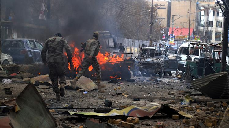 Soldiers of the Pakistani paramilitary force visit a bombing area in Quetta, Pakistan, Friday, March 14, 2014. A doctor at a hospital in southwestern Pakistan said nearly a dozen people were killed when a bomb went off near a passenger bus in the city of Quetta. (AP Photo/Arshad Butt)