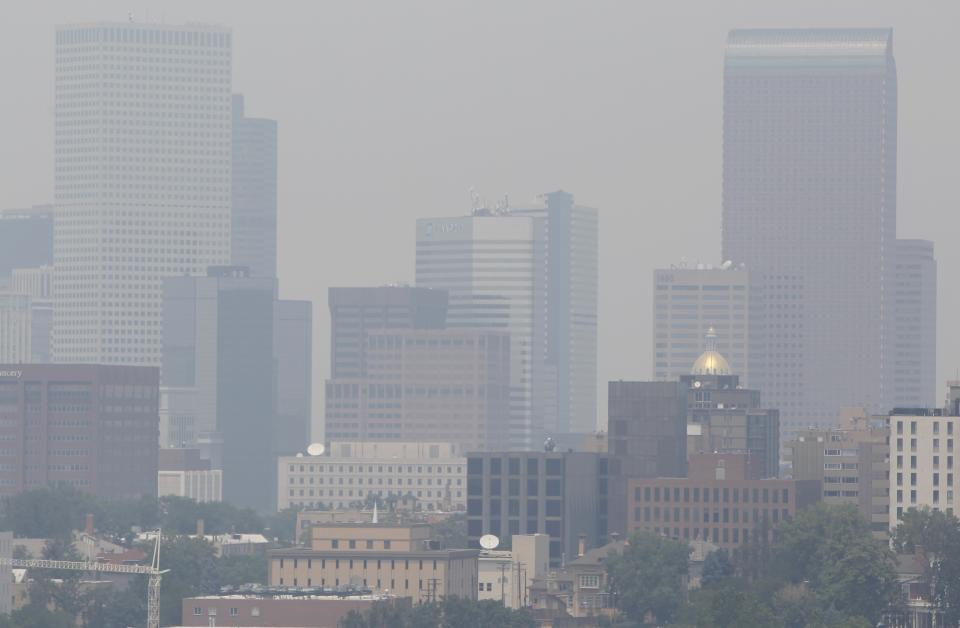 Skyscrapers in downtown Denver are obscured by smoke drifting down from fires in Wyoming, eastern Montana and western South Dakota on Wednesday, July 4, 2012. While the wildfires are contained in Colorado, states to the north are facing an uphill battle as blazes burn unabated within their borders on Independence Day. (AP Photo/David Zalubowski)