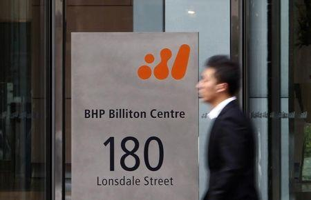 A man walks past the head office of BHP Billiton in central Melbourne