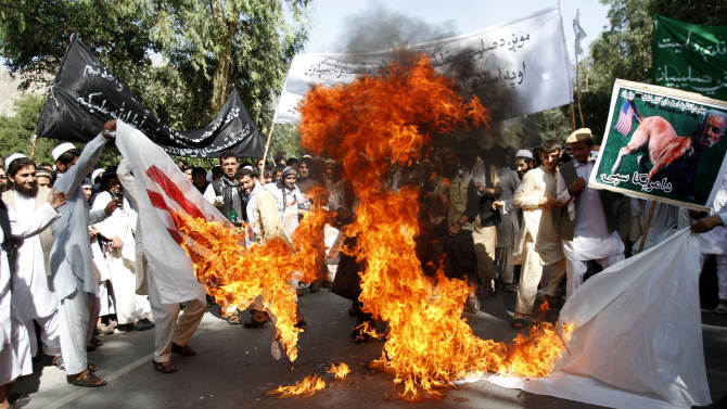 """Afghan university students burn a U.S. flag  in Surkhrod  district of Nangarhar province, east of Kabul, Afghanistan, Wednesday, Sept 19, 2012. Hundreds of Afghans, some shouting """"Death to America"""",   held a protest against an anti-Islam film in the eastern city of Jalalabad. (AP Photo/Rahmat Gul)"""