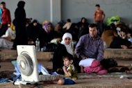 Syrian families displaced by fighting wait near Syria&#39;s border with Turkey. The rebel forces who control the Syrian side of the border oversee the area informally, ensuring that theft and assault are not a problem for now