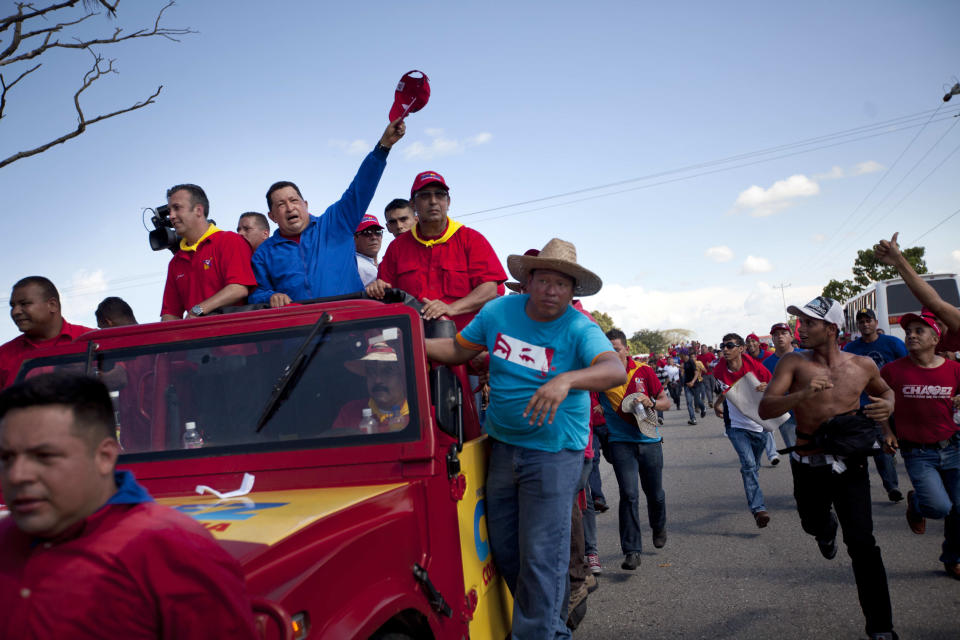 Venezuela's President Hugo Chavez waves to supporters from the of a vehicle driven by Venezuela's Foreign Minister Nicolas Maduro during a campaign caravan from Barinas to Caracas, in Sabaneta, Venezuela, Monday, Oct. 1, 2012. Venezuela's presidential election is scheduled for Oct. 7. (AP Photo/Rodrigo Abd)