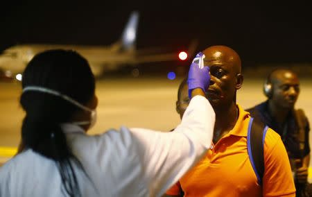 A health worker checks the temperature of a man arriving at Bata Airport