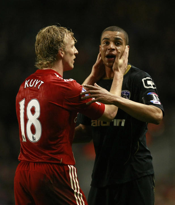 Oldham Athletic's Tom Adeyemi is calmed by Liverpool's Dirk Kuyt during their FA Cup third round soccer match at Anfield, Liverpool, England, Friday Jan. 6, 2012. The police are investigating an incid