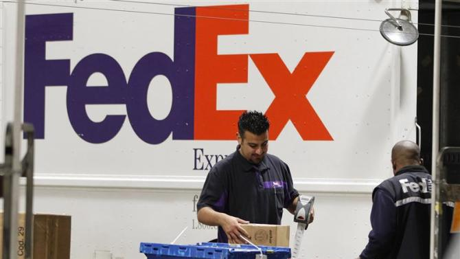 Handlers scan and affix a courier route label onto packages moving down the belt at the Marina Del Rey, California FedEx station