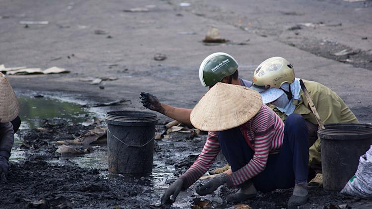 Locals collect metal fragments from the debris of a burning Chinese factory in Di An Town, Binh Duong province, Vietnam, Wednesday, May 14, 2014. Mobs burned and looted scores of foreign-owned factories in Vietnam following a large protest by workers against China's recent placement of an oil rig in disputed Southeast Asian waters, officials said Wednesday. (AP Photo/Jeff Nesmith)