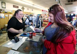 Lauren Fletcher, right, looks at the Powerball lottery …