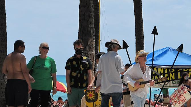 A man wearing a gas mask protested against Monsanto as a nearby ukulele player strummed a song at a Waikiki Beach rally in Honolulu on Saturday, May 23, 2015. He was part of an international day of protests against the company.  (AP Photo/Cathy Bussewitz)