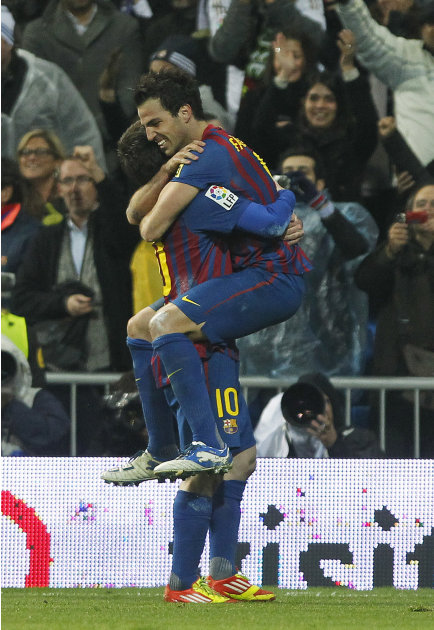 FC Barcelona's Cesc Fabregas, right, celebrates his goal with Lionel Messi from Argentina, left, during the Spanish La Liga soccer match against Real Madrid at the Santiago Bernabeu stadium in Madrid,